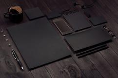 De collectieve identiteitsreeks van lege zwarte kantoorbehoeften met telefoon, koffiekop op luxe donkere houten raad, neigde Royalty-vrije Stock Foto's