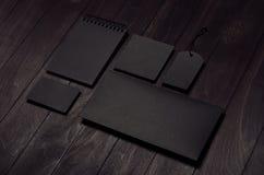 De collectieve identiteitsreeks van lege zwarte kantoorbehoeften op luxe donkere houten raad, neigde Stock Foto's