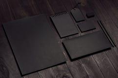 De collectieve identiteitsreeks van lege zwarte kantoorbehoeften op luxe donkere houten raad, neigde Royalty-vrije Stock Foto