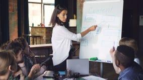 De collectieve trainer verklaart nieuwe informatie aan groep mensen, bevindt zich bij whiteboard, spreekt en richt bij stock video