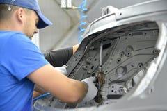 De collector werkt met het pneumatische schroefkanon bij de assemblage van Stock Foto