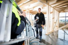 De Collega Dragende Ladder van timmermanssmiling while female bij Plaats stock foto's
