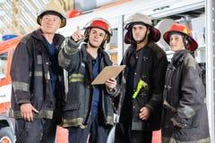 De Collega's van brandbestrijdersshowing something to Royalty-vrije Stock Afbeeldingen