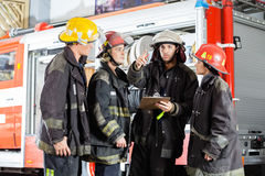 De Collega's van brandbestrijdersshowing something to bij Stock Fotografie