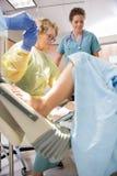 De Collega van chirurgenreceiving scissors from terwijl Stock Afbeeldingen