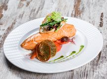 De color salm?n cocida adornada con las aceitunas, verdes, tomates en la placa sobre fondo de madera Plato de pescados caliente fotografía de archivo libre de regalías