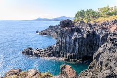 De columnar skarvarna och klipporna för Daepo Jusangjeolli basalt på Jeju Arkivbild