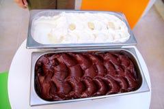 De combinatie van zwarte chocolade en wit chocolade romig die roomijs in de containers van de staaldienst op de lijst wordt ingep stock afbeelding