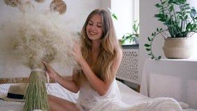 De comfortabele atmosfeer, jonge vrouw vrij van allergieën houdt boeket van veergrassen op bed in pyjama stock videobeelden