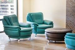 De comfortabele moderne leunstoelen en de rondetafel van het luxeleer royalty-vrije stock afbeelding