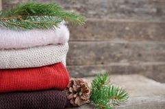 De comfortabele winter: gebreide kleren, sparren, kegels op een oude houten achtergrond stock afbeeldingen