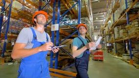 De de commerciële gang en bespreking van pakhuisarbeiders samen stock video