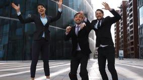 De commerciële groep jubelt, het lachen sprong met geluk stock video