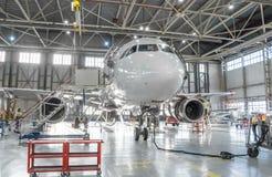 De commerciële vliegtuigenstraal op onderhoud van motor en de fuselage controleren reparatie in luchthavenhangaar stock afbeeldingen