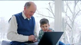 De communicatie van gepensioneerdeinternet, grootvader met kleinzoon die aan laptop en omhelzing elkaar thuis golven stock videobeelden