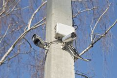 De compacte videotoezichtcamera's op steun posten op openbare gebieden op blauwe hemel Veiligheidscamera's op een pool stock foto