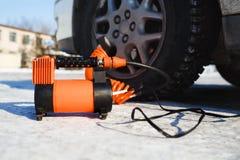 De compressor van de autolucht in het werk positie bij sneeuw Zelf-opblaast wielen, de automobiele controle van de banddruk Stock Foto's