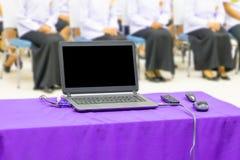 De computer op het van de lijst purpere stof en groep studentenonduidelijke beeld in klaslokaal met exemplaarruimte voegt tekst t royalty-vrije stock fotografie