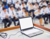 De computer op de lijst en groepsstudenten vertroebelt zitting in klaslokaal royalty-vrije stock afbeeldingen
