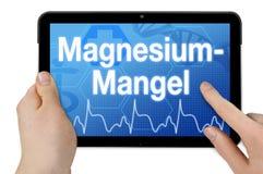 De computer van tabletcomtablet met het Duitse woord voor magnesiumdeficiëntie puter met het Duitse woord voor verslavingszorg -  royalty-vrije stock afbeelding