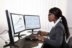 De Computers van Working On Multiple van de Effectenbeursmakelaar royalty-vrije stock afbeelding