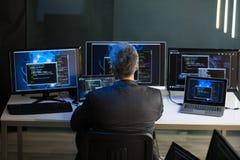 De de Computerschermen van zakenmanlooking at multiple royalty-vrije stock foto's