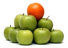 De concepten van de overheersing - sinaasappel op pyramyd van appelen royalty-vrije stock foto