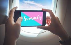 De concepten van de de zomertijd met wijfje die een foto nemen door smartphone op vliegtuig stock afbeeldingen