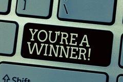 De conceptuele hand die tonend u aangaande is een Winnaar schrijven Bedrijfsfototekst het Winnen als 1st plaats of kampioen in a royalty-vrije stock afbeelding