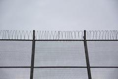 De concertina's van de kappersdraad in een grens en een blauwe bewolkte hemel Immigratie en gevangenisconcept lege exemplaarruimt stock foto's