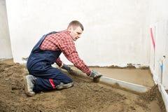 De concrete arbeider van de stukadoor aan het vloerwerk Stock Foto's