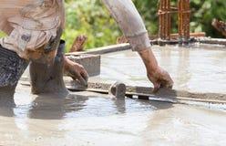De concrete arbeider van de stukadoor aan het vloerwerk Stock Afbeeldingen