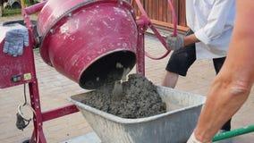 De concrete Mixer giet Gebeëindigde Oplossing in de Kruiwagen bij Bouwwerf stock videobeelden