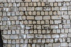 De concrete muur als achtergrond, sporen van verwering, versleten muur beschadigde verf oude verf Blijft van oude verf op geschil stock afbeelding