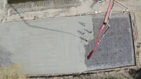 De concrete pompwerken bij de bouw De arbeiders gieten cementmortier van pomp concrete mixer De bouwers bouwen a stock videobeelden