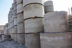 De concrete ringsputten met verschillende diameters en grijs liggen in de straat stock foto