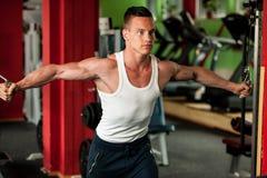 De concurrent van de lichaamsbouwgeschiktheid werkt in gymnastiek opheffende domoren uit Stock Afbeeldingen