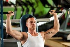 De concurrent van de Phisiquegeschiktheid werkt in gymnastiek opheffende domoren uit Stock Foto