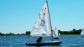 De concurrentie die, roeiend, lokale regatta op de rivier, heel wat boten verschijnt vóór het publiek, boten met zeilen varen, stock videobeelden