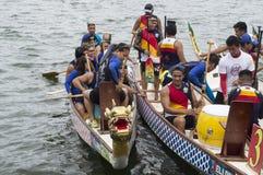 De concurrerende teams van mensen schepen op de Draak hoofdboten van de Sporten Inheemse Rij in tijdens Dragon Cup Competition stock afbeeldingen