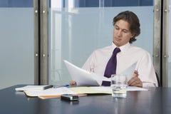 De Conferentielijst van zakenmanreviewing documents at stock fotografie