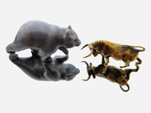 De confrontatie van stier en draagt Bronsbeeldjes van een stier en een beer in spiegelbezinning stock afbeeldingen