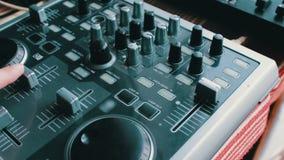 De console of de mixer van DJ, de hand drukken de hefbomen en de knopen van ver stock video