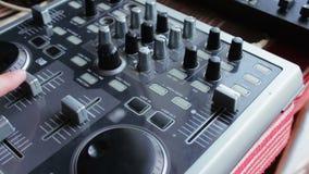 De console of de mixer van DJ, de hand drukken de hefbomen en de knopen van ver stock videobeelden