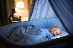 De consumptiemelk van de babyjongen in bed stock afbeeldingen