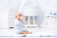 De consumptiemelk van de babyjongen in zonnig kinderdagverblijf stock foto's