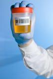De container van de urine met codestaaf op blauwe achtergrond Stock Afbeeldingen