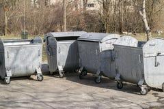 De container van het metaalafval met wielen Vier lege huisvuilbak De bak van het huisvuil royalty-vrije stock afbeeldingen
