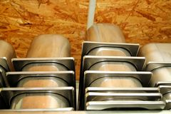 De containers van de staaldienst voor roomijs op stapels op de plank wordt ingepakt die Industriële voorbereiding van romig roomi royalty-vrije stock fotografie
