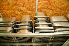 De containers van de staaldienst voor roomijs op stapels op de plank wordt ingepakt die Industriële voorbereiding van romig roomi royalty-vrije stock foto